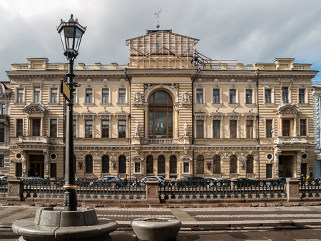 The facade of the historical building of the construction bank of the beginning of the twentieth century, decorated with statues, bas-reliefs, arched windows, atlantes, patterned cornices, friezes on the Griboedov channel in St. Petersburg