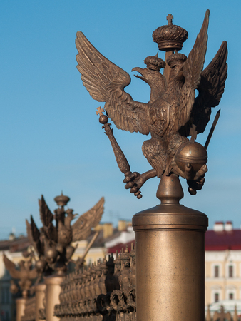 Figure of the three-headed eagle in the imperial crown on the fence of the pillar of Alexandria on Palace Square in the center of St. Petersburg, Russia