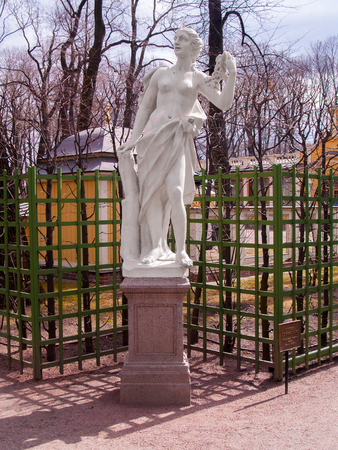 A statue of a woman with a garland of roses in a park A summer garden near a green trellis near a sand track against a yellow background in the early spring in April before the opening of the summer park season in St. Petersburg Stock Photo