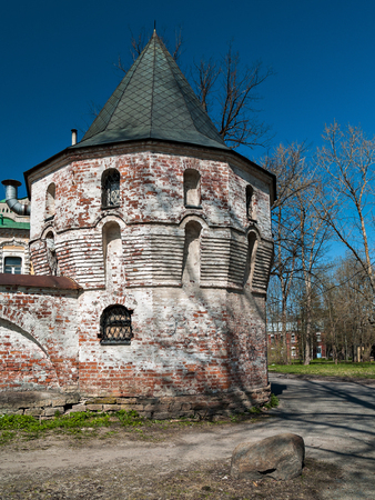 White corner tower of red brick with a green pointed roof in a ruinous architectural ensemble Fedorovsky town in the Alexander Park in Tsarskoye Selo in St. Petersburg, Russia