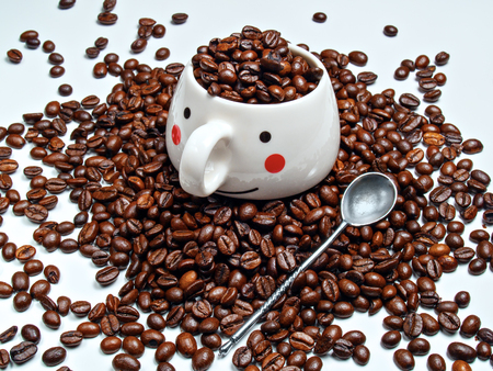 A coffee mug with grains of roasted coffee and a spoon next to it are placed on roasted coffee beans