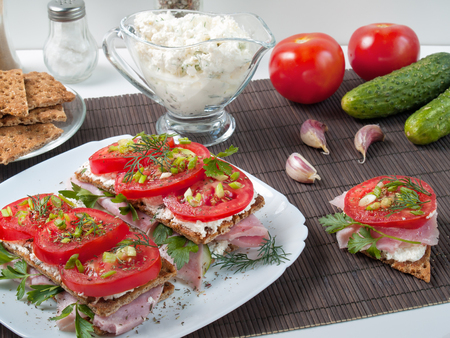 Sandwiches with rustling bread from buckwheat flour smeared with curd cheese on top is ham, tomato with greens and spices is shown close up Stock fotó