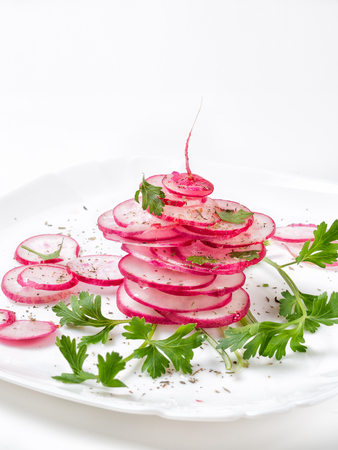 Salad of fresh radish cut with sticks carefully neatly laid on a white plate topped with herbs and spices with lemon juice and olive oil Stock Photo