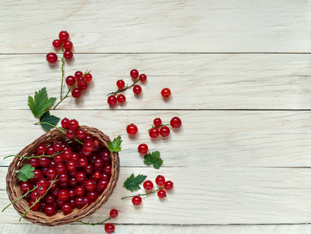 Fresh and large berries of red currant are in a wicker basket on a wooden background are shot from above close-up Stock Photo