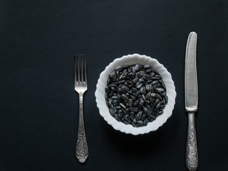 On a dark background there is a white round cup with sunflower seeds next to it lie a knife and fork lifted from above by a close-up