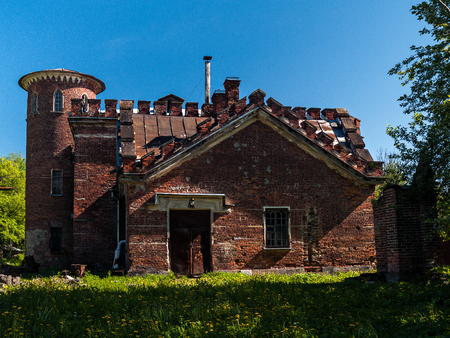 The facade of the building of the old stables of red baked brick with a round turret, crenellated roof and annexes in English style on a green glade in summer on a sunny day in Alexander Park in Pushkin, St. Petersburg, Russia