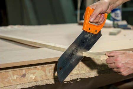 handsaw: man handsaw sawing material Stock Photo