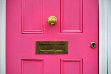 detail of pink door with letterbox,