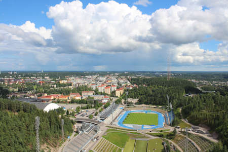 View of the stadium, forest and city of Lahti against the sky with clouds. Finland.
