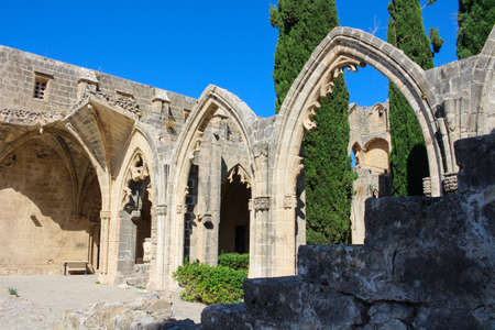 Arches of Bellapais Abbey, White Abbey, Abbey of the Beautiful world. Cypress trees against a blue sky.