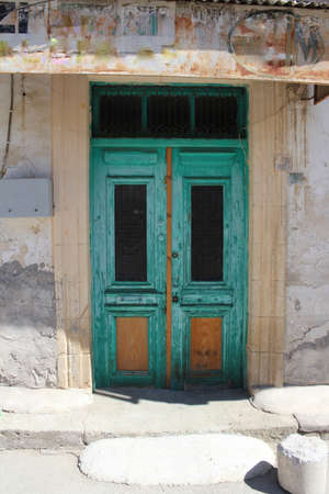 Original green wooden door with forged elements. Cyprus.