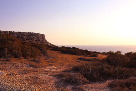 View from below on the red stony soil and Cape Cavo Greco (Capo Greco) in the sunset. Cyprus.