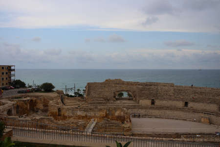 Top view of the Roman amphitheater of Tarraco in Tarragona against the sea and sky, Catalonia, Spain.