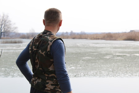 The man stares into the distance while standing on the shore of the lake.