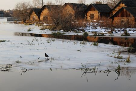 old village on the Bank of the river with ice in the evening Stockfoto