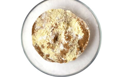 Flour and brown sugar in the transparent plate. White background.