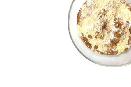 White background with flour and brown sugar in the transparent plate.