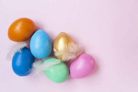 Pink, golden, orange, blue, green eggs. Copy space. Place for text and design. Top view. Flat layout.