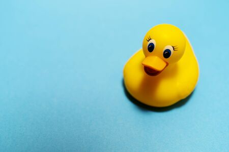 Children's bath rubber yellow duck on the blue background. Swimming concept. Minimal idea. Copy space. Place for text and design.