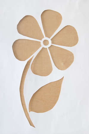 Silhouette of a flower carved on a piece of paper, which is on a wooden surface photo