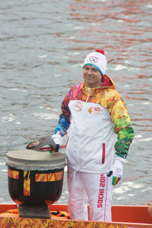 olympic symbol: TVER, RUSSIA - OCT 11  Torchbearer Ignat Kovalev on a boat with a dragons head on October 11, 2013  The main symbol of the Olympic Games sailed down the Volga river, accompanied by two hundred vessels