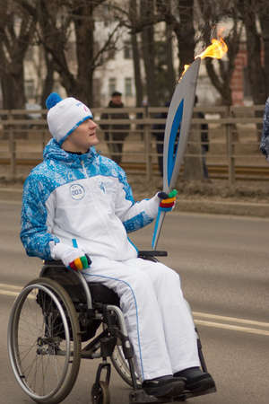 paralympic: TVER, RUSSIA - MARCH 2, 2014  Torchbearer in a wheelchair with a torch on the Paralympic Torch Relay