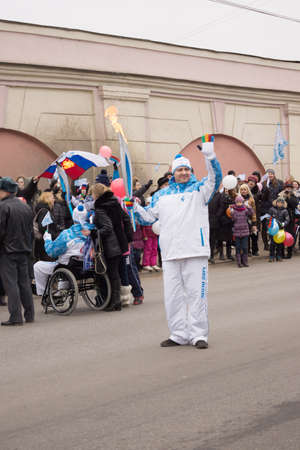 paralympic: TVER, RUSSIA - MAR 2, 2014: Torchbearer with torch in hand on the Paralympic Torch Relay. In the Paralympic Torch Relay in Tver involved 100 torchbearers