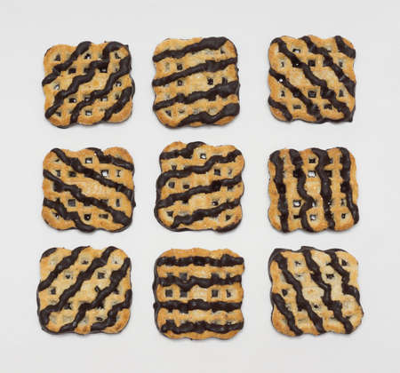 chocolate icing: Nine cookies covered with chocolate icing on a white background Stock Photo