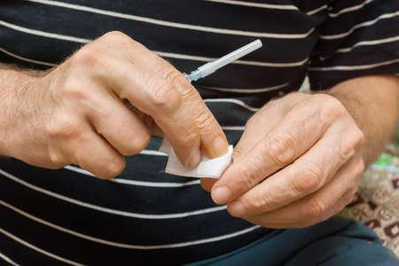 desinfectante: El hombre frota con desinfectante toallita ampolla con medicamentos para hacerse un pinchazo