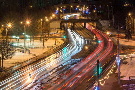 light trail: Blurred Tail Lights And Traffic Lights On Road Stock Photo