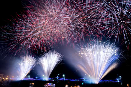 Fireworks launched from a bridge in the night sky in the city taken at slow shutter speeds Stock Photo