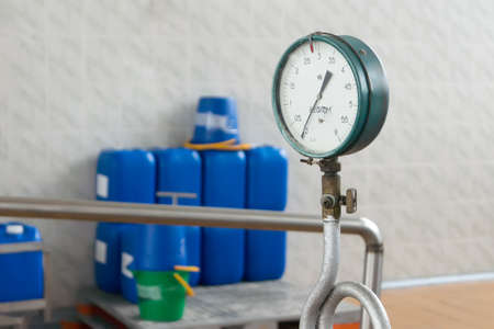 Measuring instrument screwed to the pipe on a background of blue cans at a factory