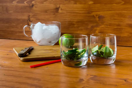 The cut ingredients for a mojito cocktaill in a glass on a wooden table