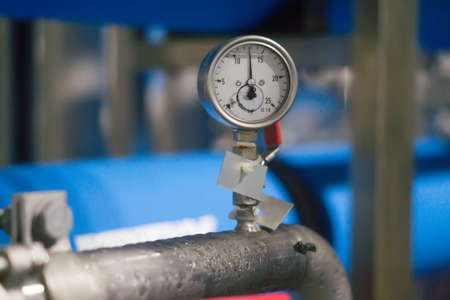 condensate: Measuring device bolted to a metal pipe with condensate Stock Photo