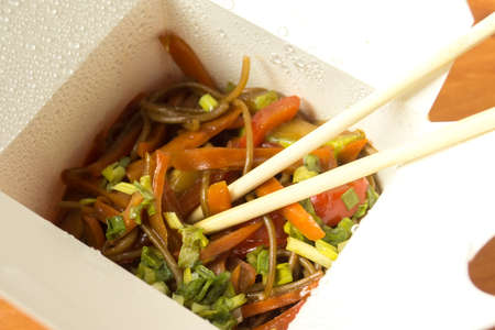 Open box with noodles, vegetables, sauce and chopsticks.