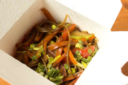 Open the packaging with a mixture of noodles, vegetables and sauce, ready for delivery.