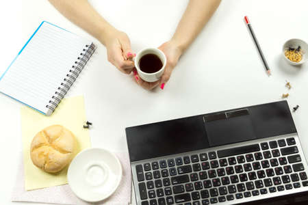 The girl holding a white cup with coffee over a work space.