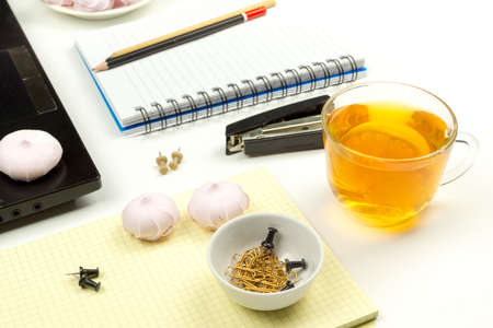 Stationery, marshmallows, tea on the background of the workplace. Stock Photo