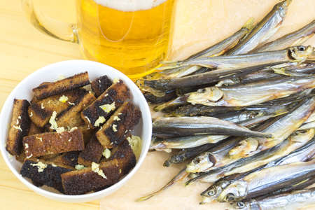 With garlic croutons next to the mug of light beer and dried fish.