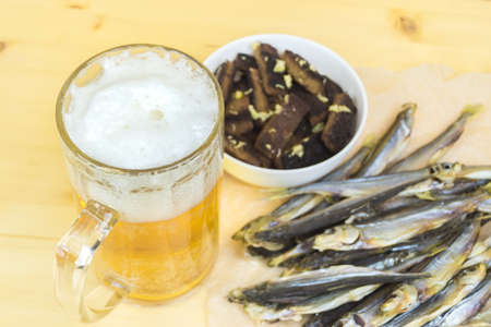 potation: Mug with a frothy beverage, crackers, dried fish on a wooden surface.