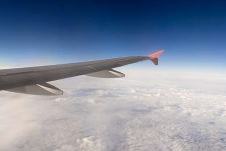 Wing of an airplane above solid clouds Stock Photo