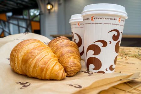 Svetlogorsk, Kaliningrad region, Russia - Oct 17, 2017: Two cups of coffee and two croissants on the street in Croissant Cafe. Inscripton on cup - Croissant Cafe Editorial
