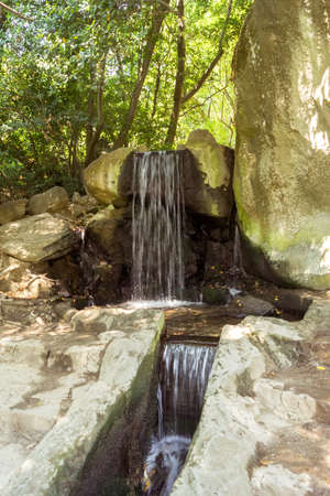 Waterfall in the rocks on a sunny summer day in the park 版權商用圖片