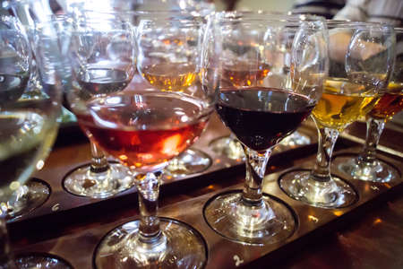 Glasses filled with various wine on table at tasting