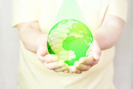An elderly woman is holding a green holographic Earth. Futuristic concept