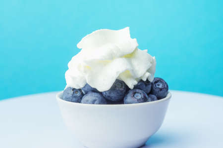 Fresh blueberries with whipped cream against blue background