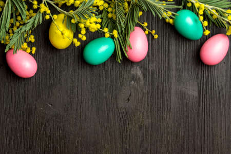 Easter background with mimosa, eggs and wooden surface, celebration