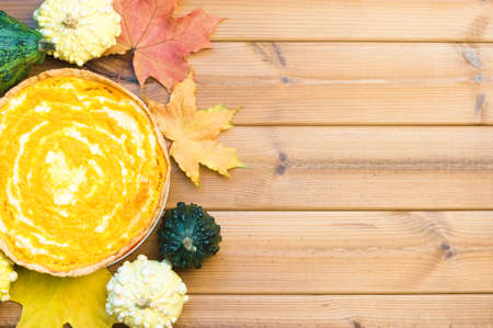 Festive wooden table with pumpkin pie and maple leaves. Happy thanksgiving day