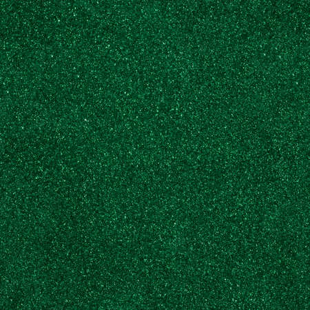 Surface texture with green sparkles. Seamless festive background. Dark evening backdrop