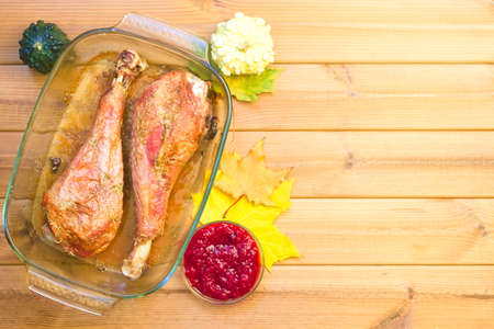 Festive wooden table with turkey drumsticks, pumpkin pies and maple leaves. Happy thanksgiving day Stockfoto